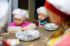 Alchevsk, Ukraine - January 21, 2018: Children in the form of cooks learn how to cook lasagna.  Stock Photography