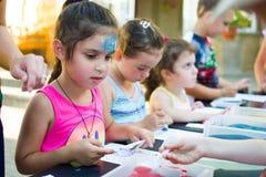 Alchevsk, Ukraine - 27 juillet 2017 : Les enfants peignent avec la colle et le sable coloré Partie du ` s d'enfants Photographie stock