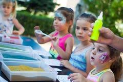 Alchevsk, Ukraine - 27. Juli 2017: Kinder malen mit Kleber und farbigem Sand Kind-` s Partei Lizenzfreie Stockfotografie