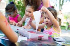 Alchevsk, Ukraine - 27. Juli 2017: Kinder malen mit Kleber und farbigem Sand Kind-` s Partei Stockbild