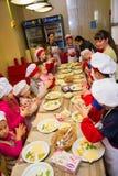 Alchevsk, Ukraine - 15. Oktober 2017: Schulköche für Kinder in einem Café Zubereitung der Fruchtpizza Stockfotografie