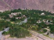 Alchi山村在拉达克谷的:白色房子和寺庙在小山、绿色树和领域,河床o 库存图片