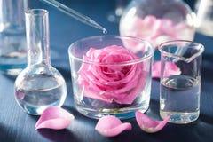 Alchimie en aromatherapy met roze bloemen en chemische flessen stock fotografie