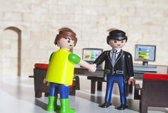 Alcobendas, Espa?a 12 de octubre de 2018 apret?n de manos entre de dos mangos, en una oficina La l?nea del juguete de Playmobil e fotografía de archivo