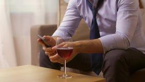 Alcohólico con el vino de consumición del smartphone en casa almacen de video