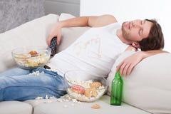 Alcohólico que duerme en el sofá imagenes de archivo