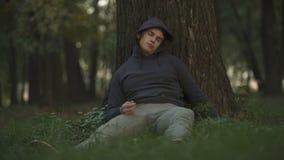 Alcohólico vulnerable que duerme debajo de árbol en la juventud del parque, descuidada y loca almacen de metraje de vídeo