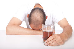 Alcohol. Man putting his head on a table and holding an alcoholic beverage in his hand Stock Photos