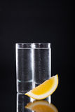 Alcohol. Shot glass filled with clear alcohol on a black background stock images