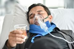 Drunk man with Alcoholism. Alcohol addicted businessman with oxygen mask is holding whiskey glass while lying on hospital bed. Sad depressed patient male adult stock photo