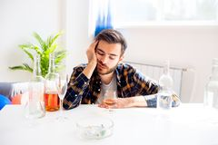 Alcohol addicted man. Is drinking alone at home stock images