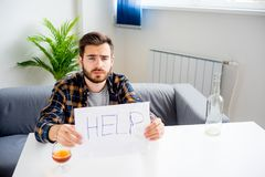 Alcohol addicted man. Is holding a help sign Stock Photography