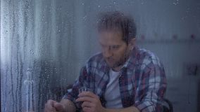 Alcohol addicted man drinking vodka in loneliness behind rainy window, problems. Stock footage stock video footage