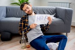 Alcohol addicted man. Is holding a help sign stock images