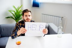 Alcohol addicted man. Is holding a help sign stock image