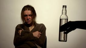 Alcohol addicted woman looking at bottle of vodka, undergoing rehabilitation royalty free stock image