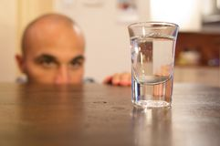Alcohol addiction. Addicted man looking at a glass filled with alcohol Royalty Free Stock Image