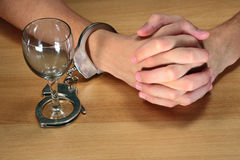 Alcohol addiction. Hands handcuffed with an empty alcohol glass Royalty Free Stock Images