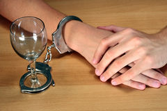 Alcohol addiction. Hands handcuffed with an empty alcohol glass Royalty Free Stock Photos