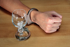 Alcohol addiction. Hands handcuffed with an empty alcohol glass Royalty Free Stock Image