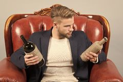 Alcohol addiction, bad habits. Man choose wine to drink. Guy with bottles of wine sit on brown leather armchair. Choice, decision concept stock photos