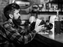 Alcohol addiction loneliness. Hipster holds wallet, counting money to buy drinks. Depressed and sad man sit alone in bar or pub near bar counter royalty free stock photo