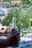 Alcohol addiction, man's hand keeping bottle with white wine on. Outdoor terrace in sunny day stock photo