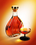 Alcohol in bottles with glass on yellow background. Alcohol cognac in bottles with a glass on yellow gold background Stock Photo