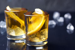 Alcohol cocktail with brandy, whiskey, lemon and ice in small glasses Stock Photos