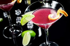Alcohol cocktail Cosmopolitan. Alcohol drink cocktail Cosmopolitan with lime on black background royalty free stock photos