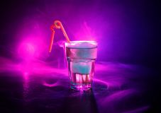 Alcohol cocktail in glass with ice in smoke on dark background. Club drinks concept. One glass of cocktail. Selective focus royalty free stock photo