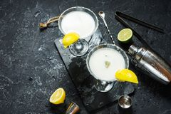 Alcohol cocktail margarita on a black stone table, with lemon. lime and shaker.  Stock Images