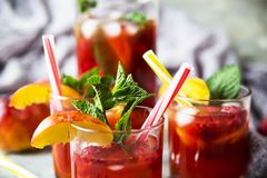 Alcohol cocktail for a summer party. Light summer refreshing drink with fruits and berries - sangria. In glasses on a gray table Stock Images