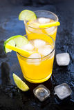 Alcohol cocktails with lime and ice on dark background Stock Images