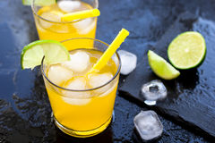 Alcohol cocktails with lime and ice on dark background Royalty Free Stock Images