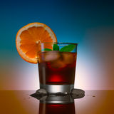 Alcohol coctail drink with ice cubs and orange on a color background. Alcohol coctail drink with ice cubs on a color background Royalty Free Stock Image