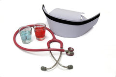 Alcohol in cup and stethoscope or nurse hat. On white backgraund stock photos