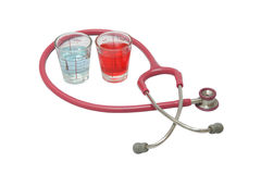 Alcohol in cup and stethoscope Stock Images