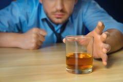 Alcohol de consumición del hombre borracho en la tabla imagen de archivo libre de regalías