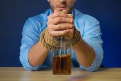 Alcohol de consumición del hombre borracho en la tabla imagenes de archivo