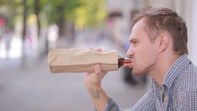 Alcohol de consumición del hombre desaliñado en la calle cerveza en una bolsa de papel almacen de video