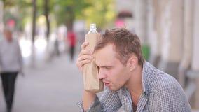 Alcohol de consumición del hombre desaliñado en la calle cerveza en una bolsa de papel almacen de metraje de vídeo