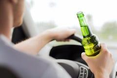 Alcohol de consumición del hombre mientras que conduce el coche imagen de archivo libre de regalías