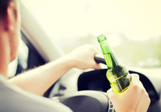 Alcohol de consumición del hombre mientras que conduce el coche imagen de archivo