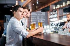 Alcohol de consumición en una barra Tres hombres de los amigos que beben la cerveza y h Imagen de archivo