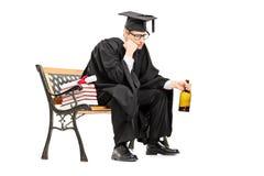 Alcohol de consumición triste del graduado de universidad asentado en banco Imagen de archivo libre de regalías