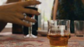Alcohol de la bebida de la gente en terraza El hombre vierte el coñac en vidrio corto en la tabla aclamación almacen de video