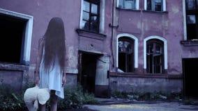 Alcohol de una muchacha con el pelo largo cerca de la mansión vieja fantasma del bebé metrajes