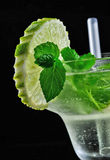 Alcohol drink, cocktail with mint, lemon, strows, isolated black. Alcohol cocktail drink with lemon, isolated black background Royalty Free Stock Photography