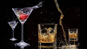 Alcohol drinks. With splashes, isolated on black background royalty free stock photography